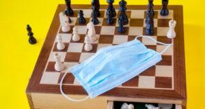 Настольная игра, деревянные шахматы и медицинская маска на желтом фоне